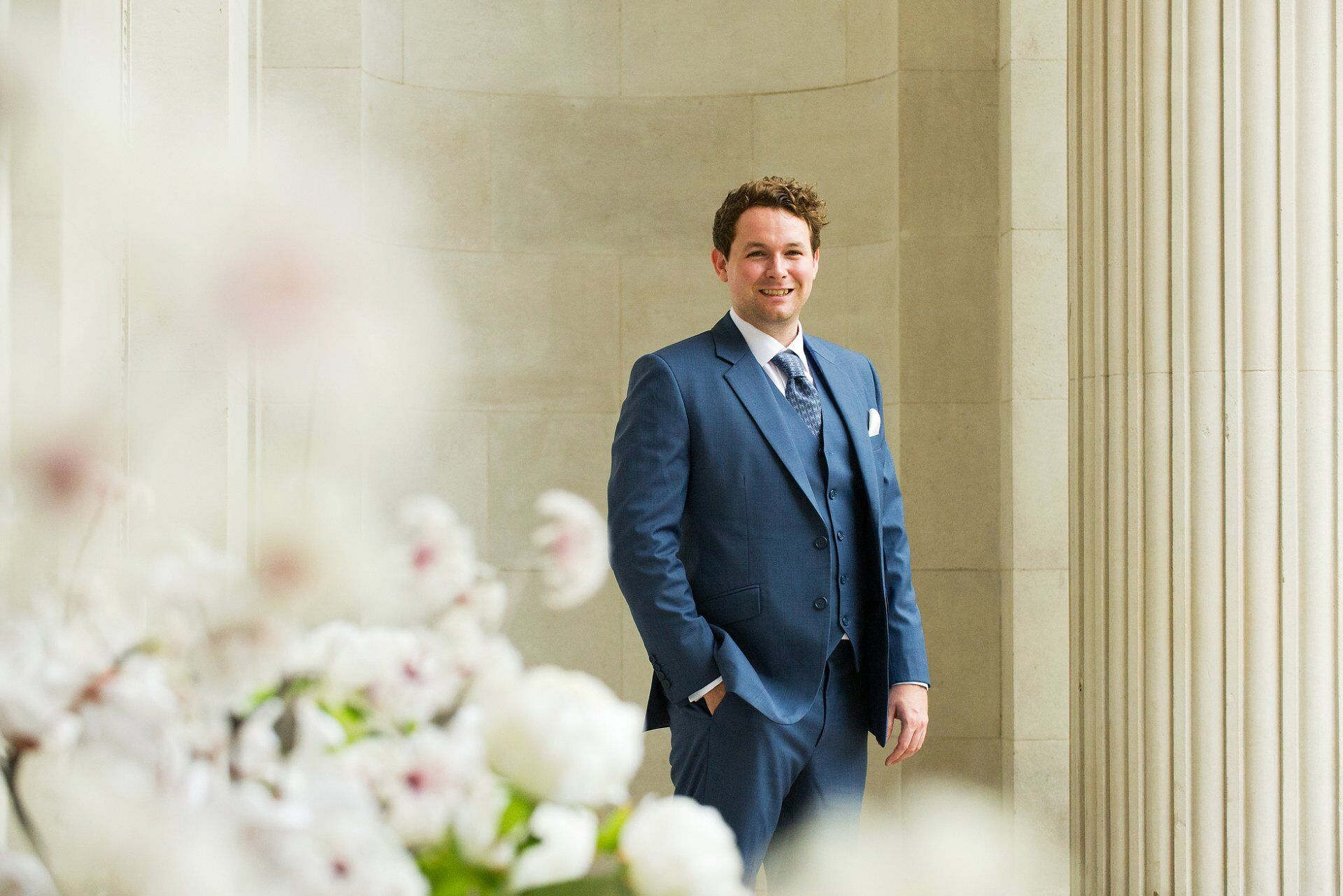 groom wearing blue three piece suit and blue tie at old marylebone town hall just before ceremony in the soho room wedding photography by emma duggan