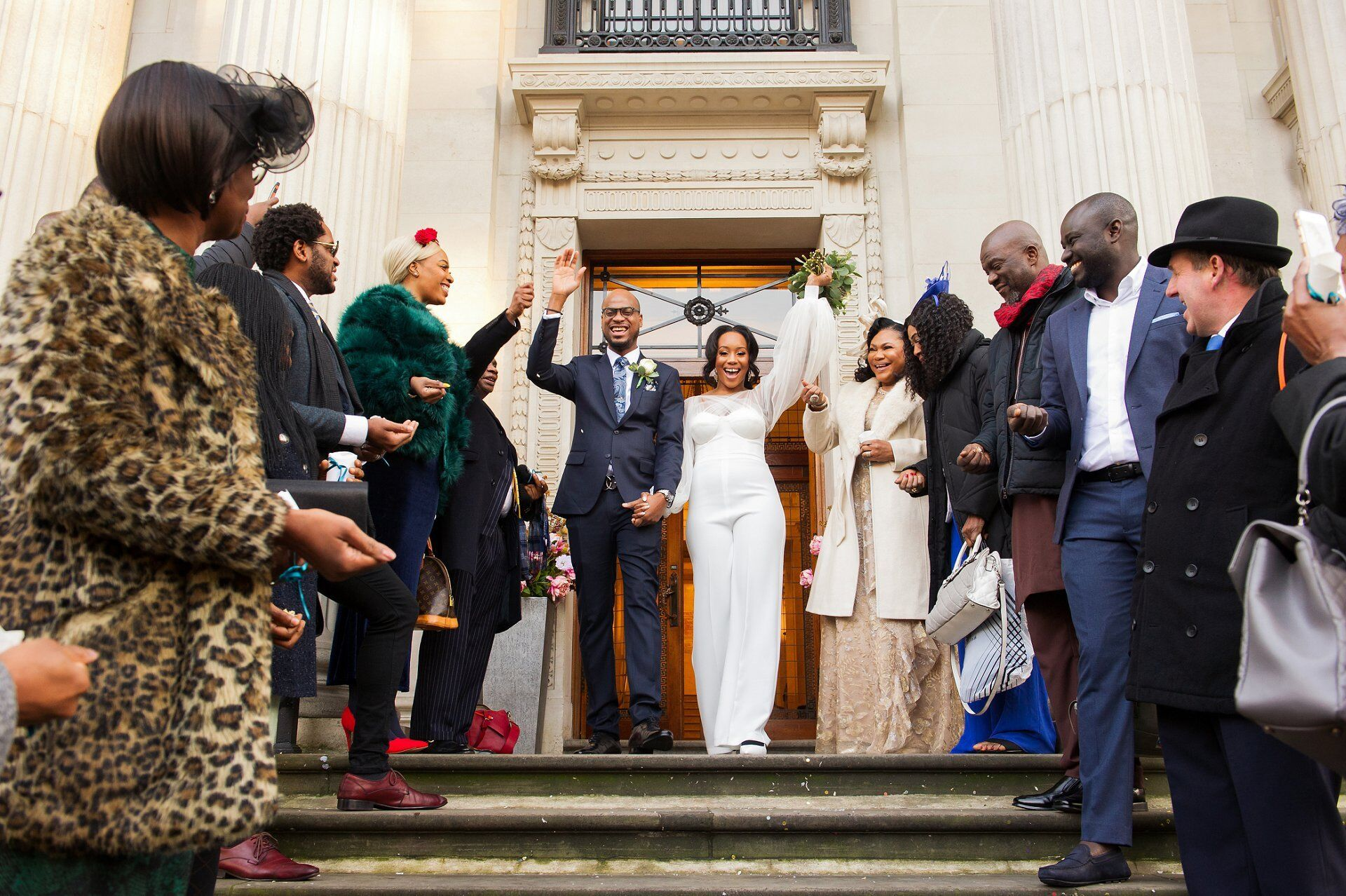 bride and groom celebrate as they leave old marylebone town hall down the famous steps outside