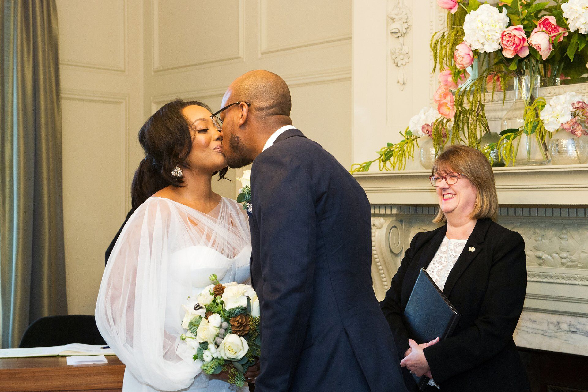 bride and groom kiss to seal the deal with registrar looking on and smiling
