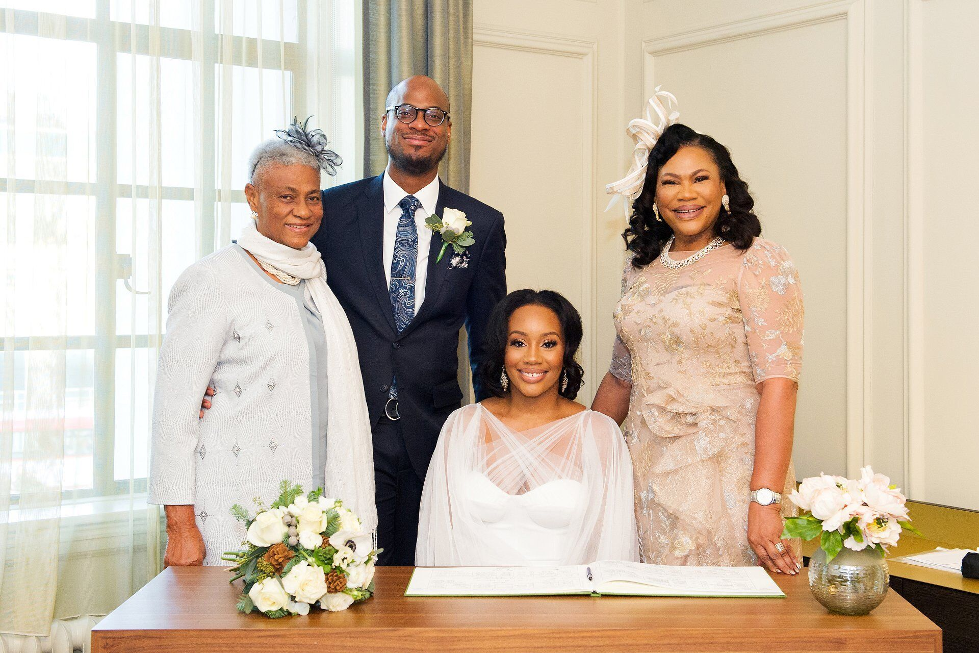 bride and groom plus their mothers - the witnesses - pose for a formal photograph