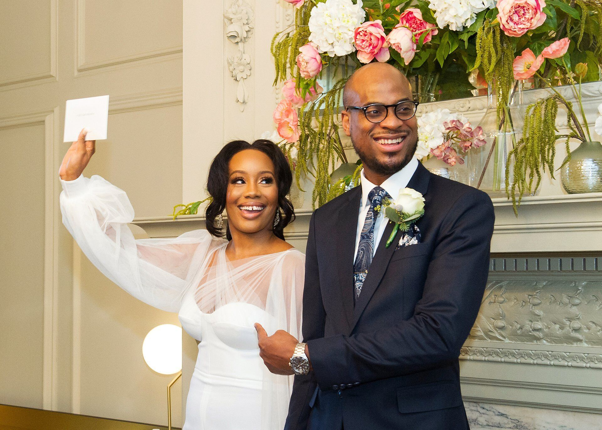bride holds their marriage certificate aloft as groom looks towards guests, smiling