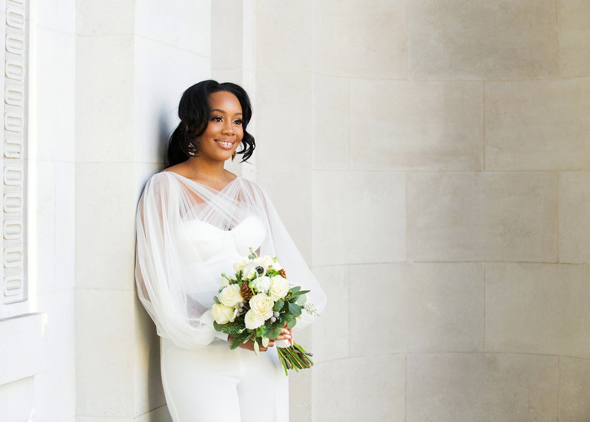 old marylebone town hall wedding photography nigerian bride in white jumsuit under the portico at westminster council house