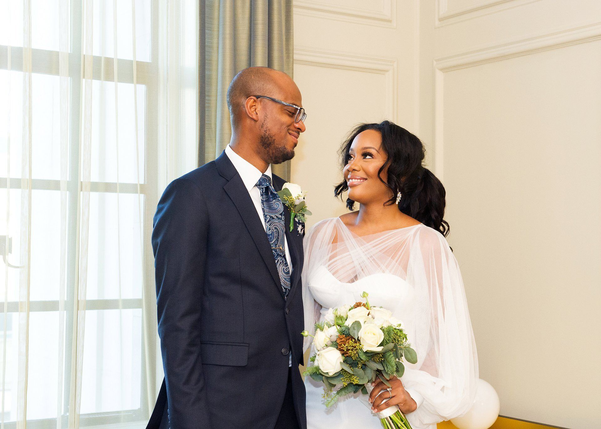 we did it - a couple smile at each other during their civil wedding at old marylebone town hall