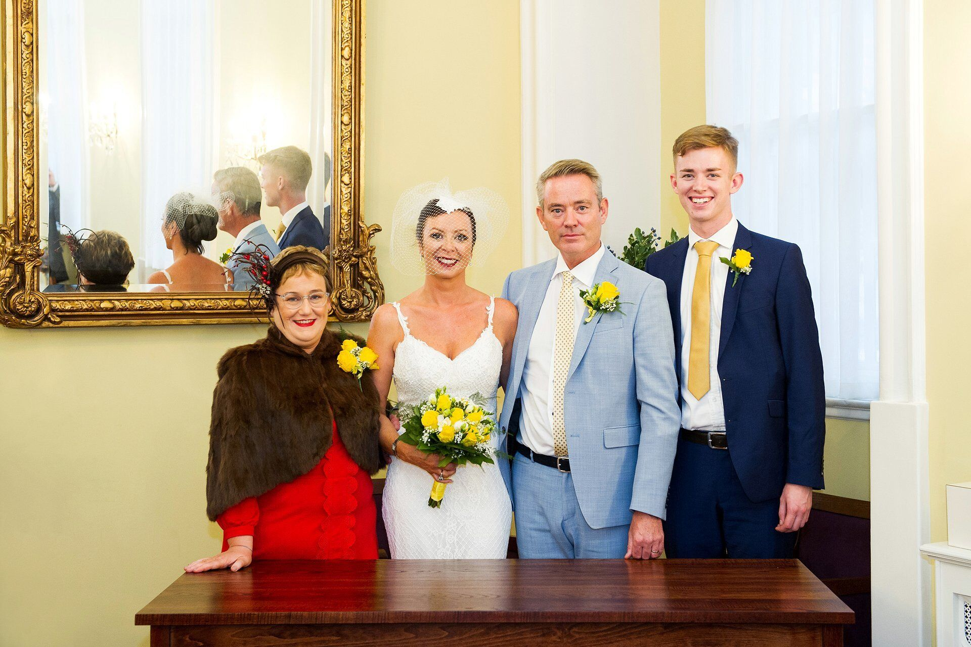 bride and groom and their two witnesses pose for a photograph in the brydon room at chelsea old town hall