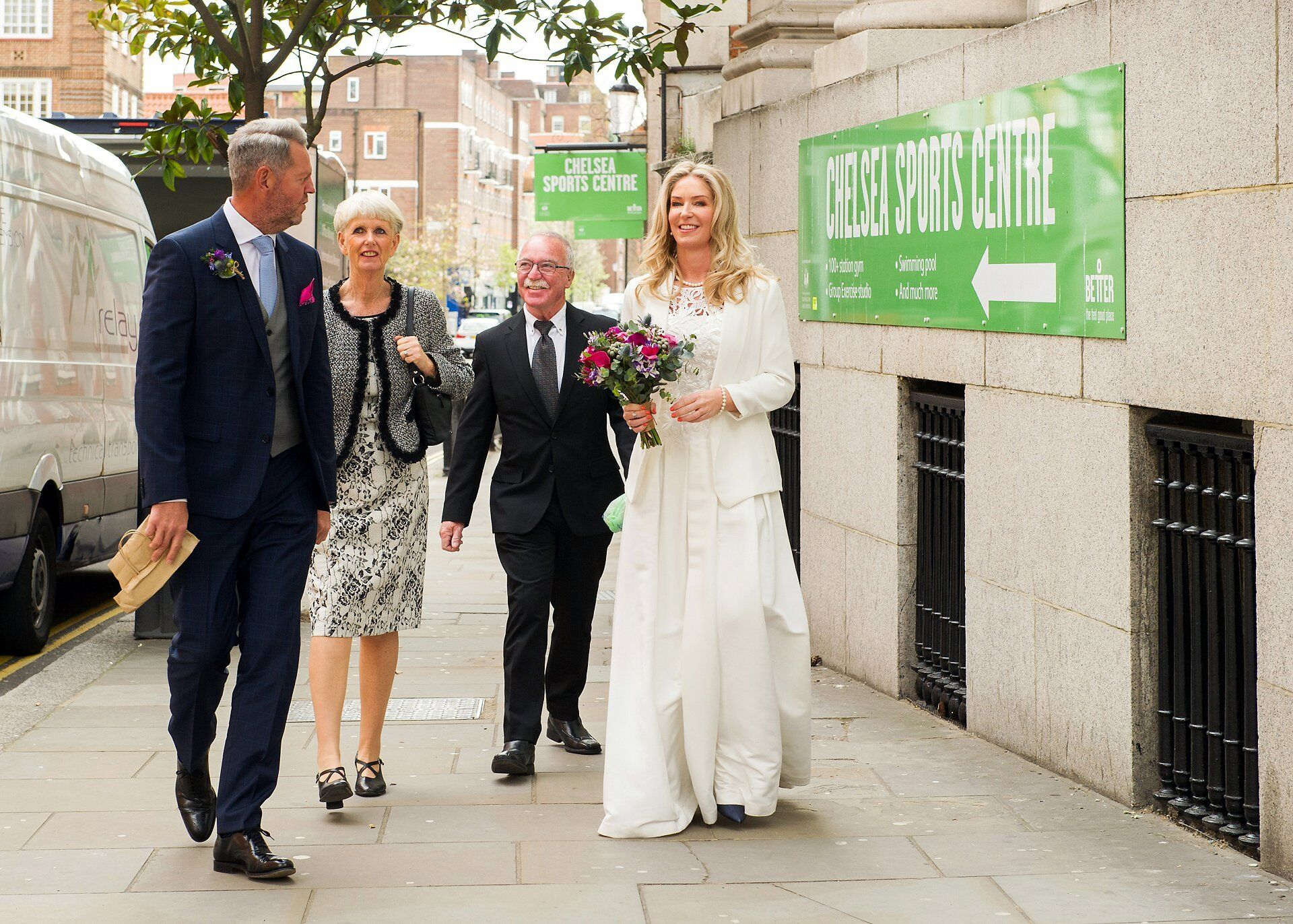 bride and groom approaching the newly reopened chelsea old town hall right next to chelsea sports centre