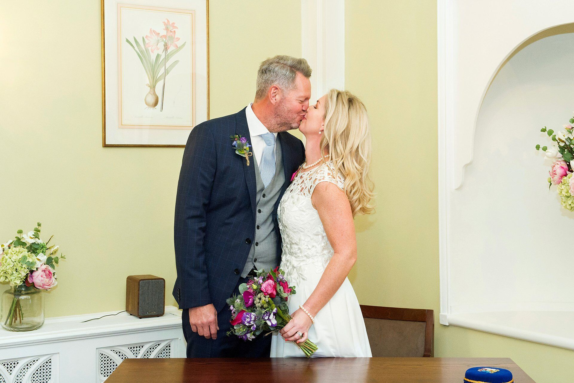 bride and groom kiss to celebrate their marriage in the rossetti room at chelsea register office