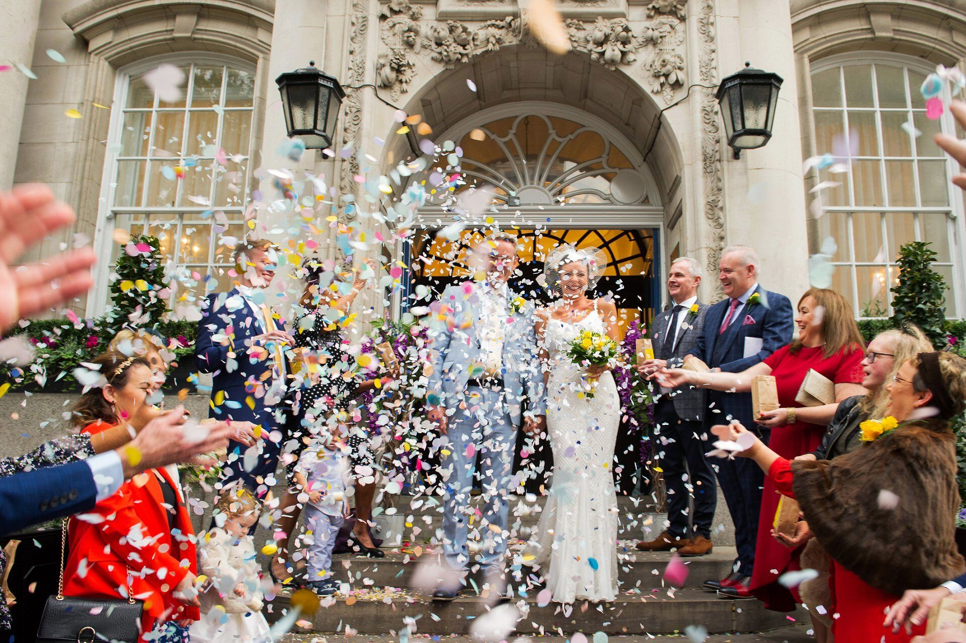 bride and groom on the famous steps at chelsea old town hall under a mass of pastel paper confetti
