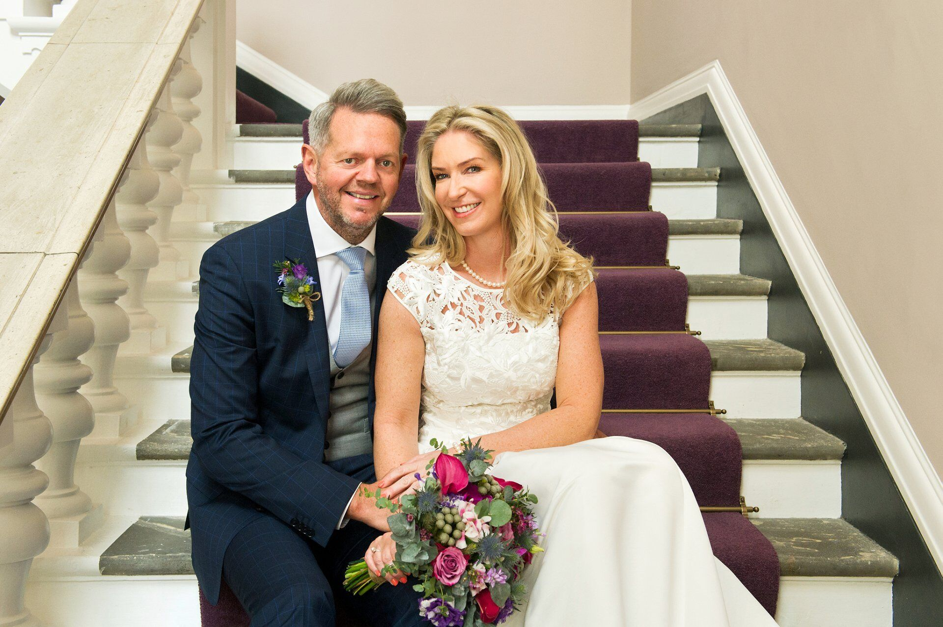 bride and groom pose on the newly refurbished staircase chelsea old town hall wedding photographer at the chelsea old town hall reopening in spring 2019