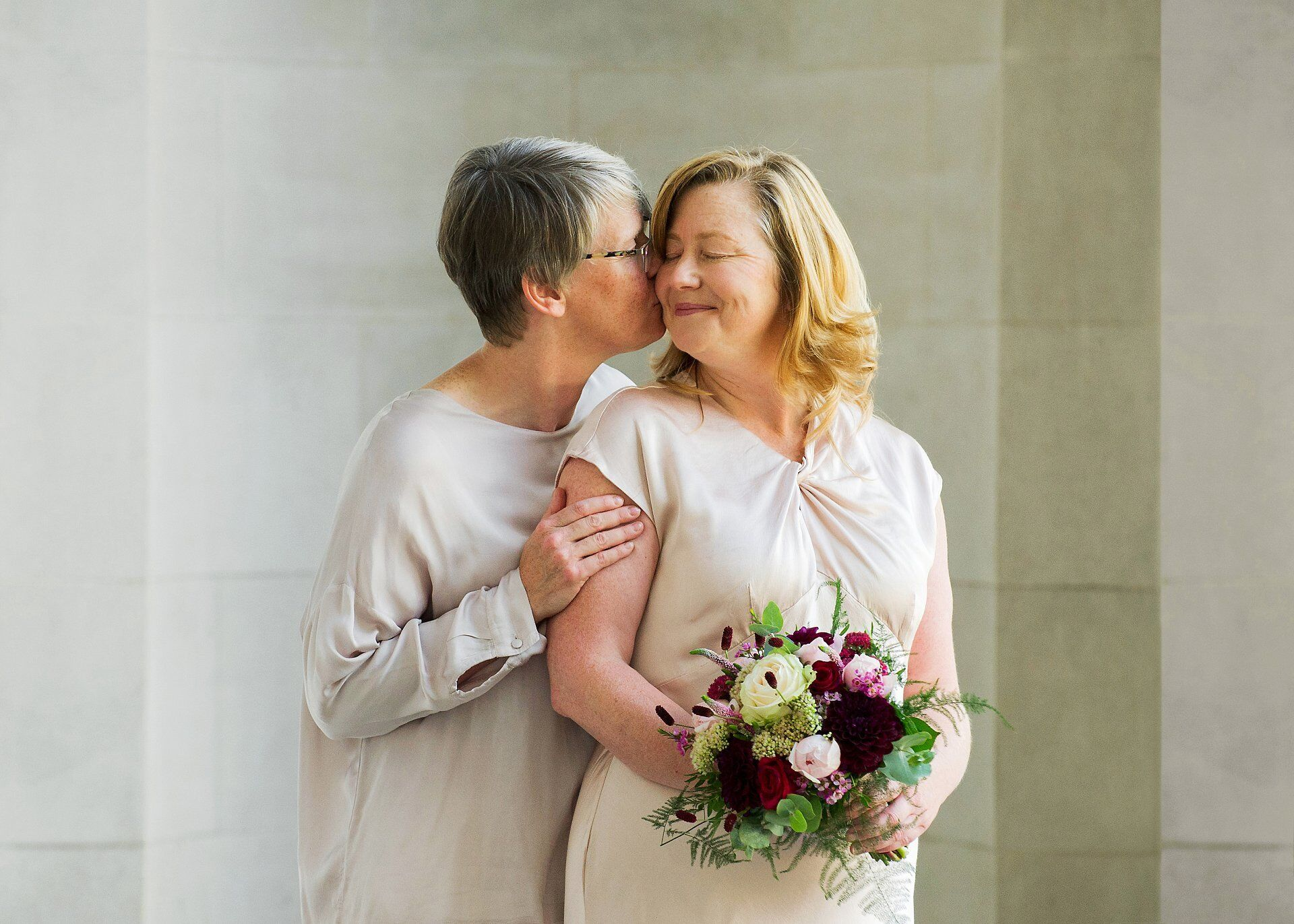 bride sarah kisses her wife to be emma under the fluted columns at a day to remember westminster