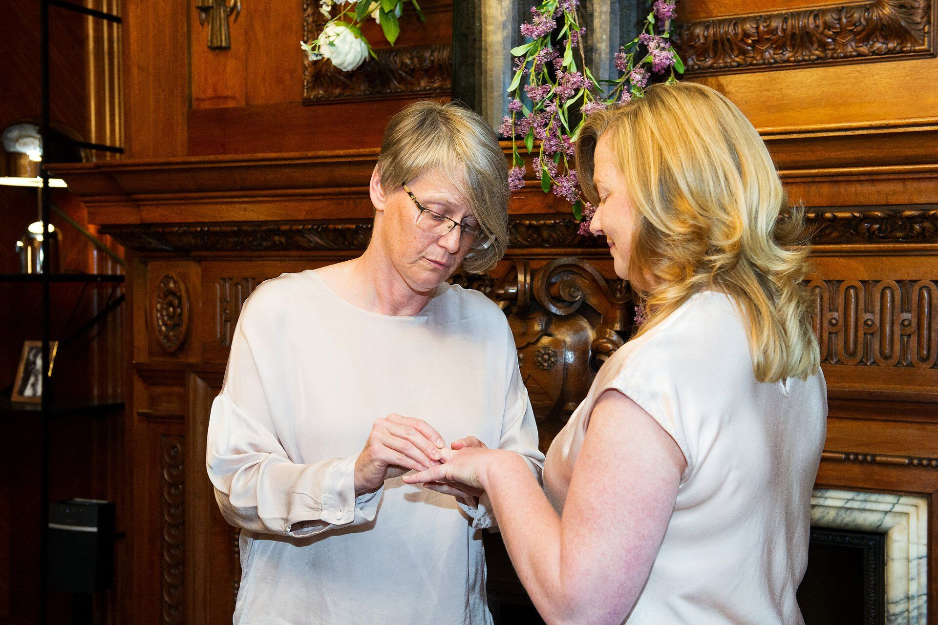bride sarah places the ring on emma's finger after their wedding vows in marylebone's paddington room