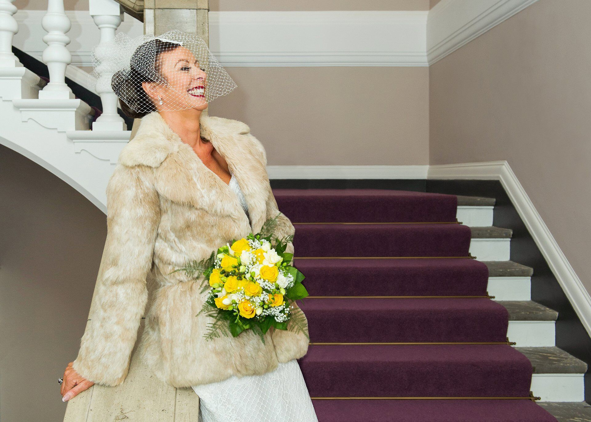 bride with fur jacket and birdcage veil smiles before her chelsea old town hall wedding ceremony