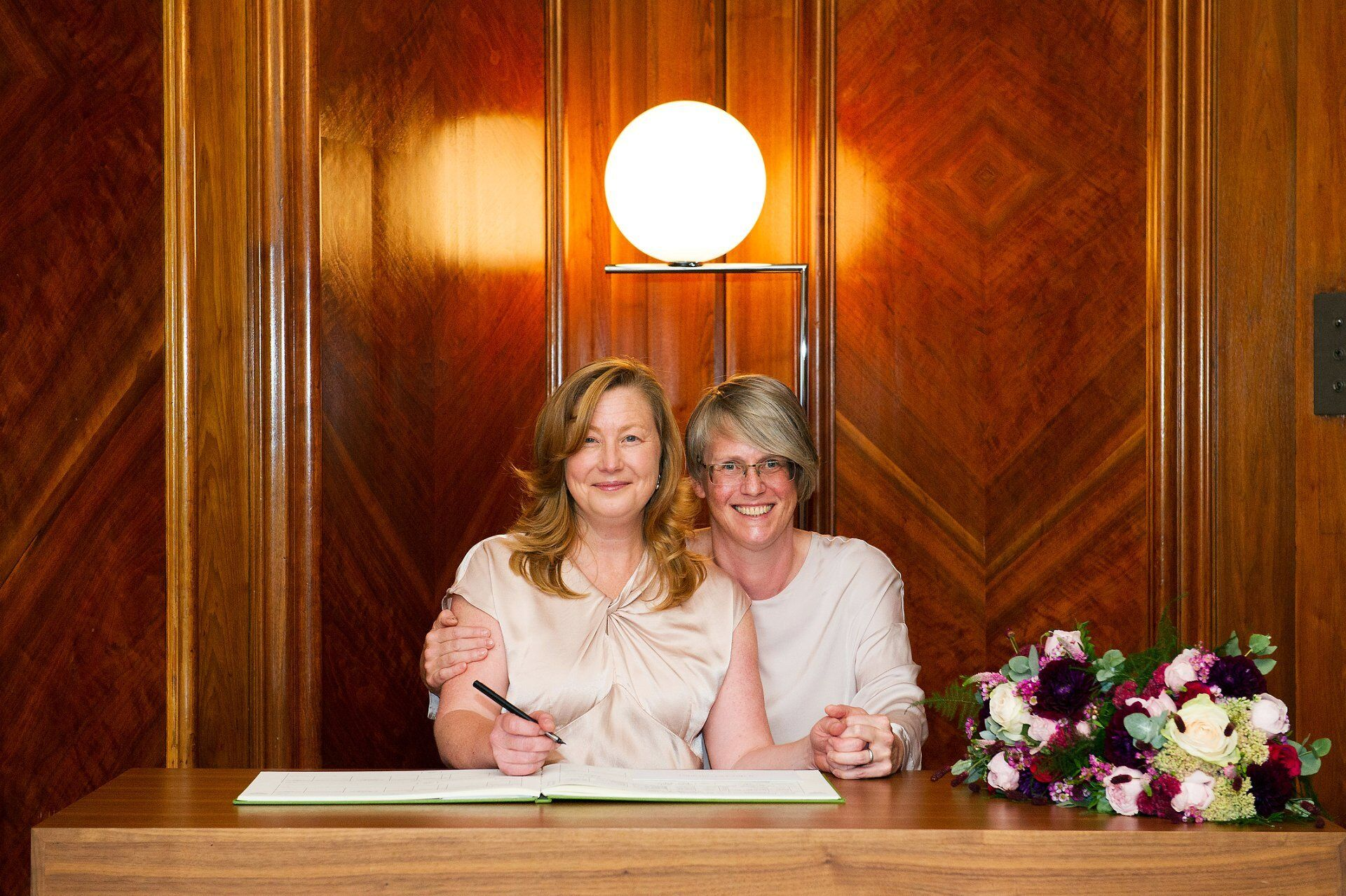 brides posing with the register in the paddington room with their stunning tatiana's garden flowers (perfect covid-19 social distancing city wedding venue in london)
