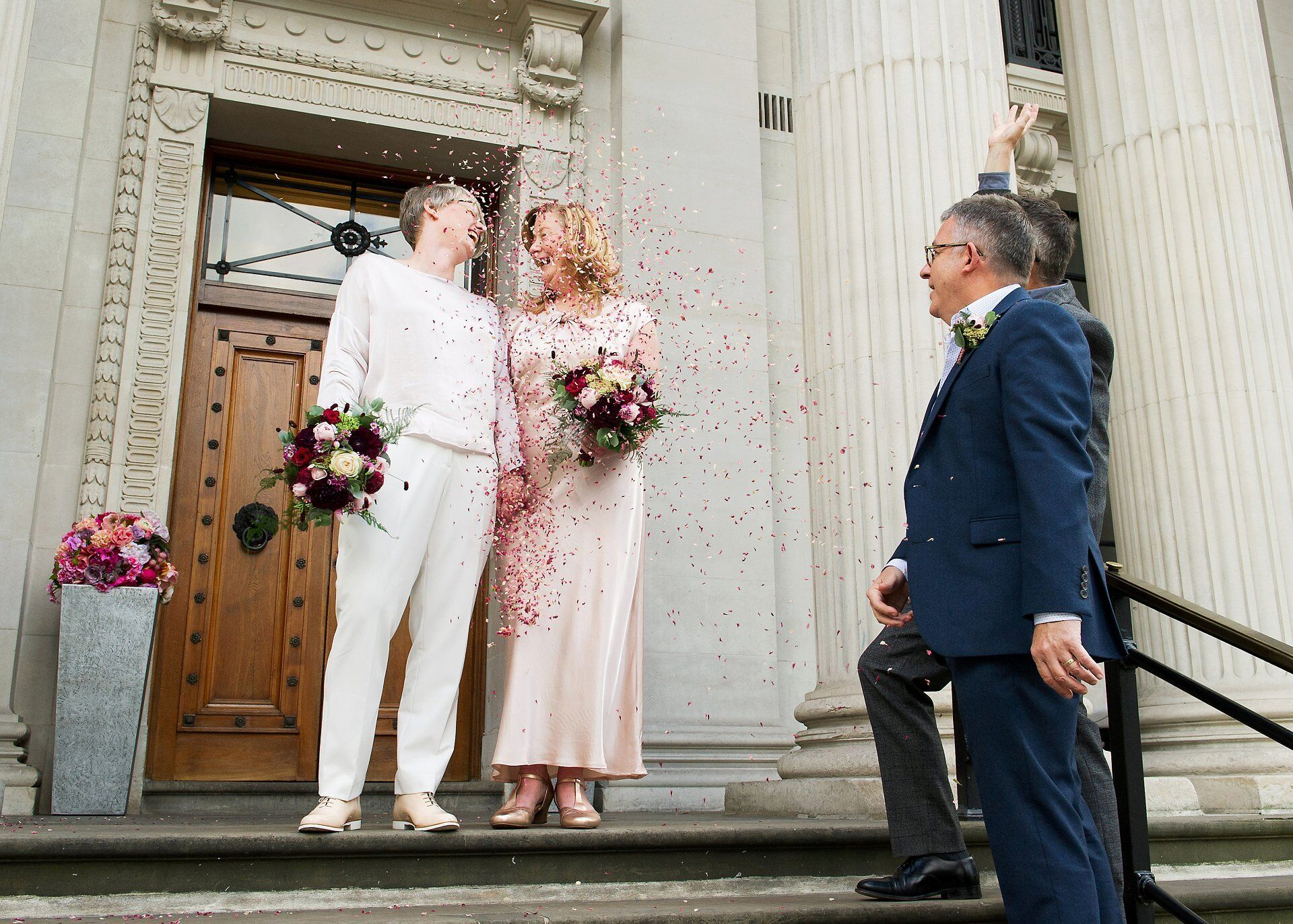 confetti from shropshire petals throw by guests over two brides leaving old marylebone town hall