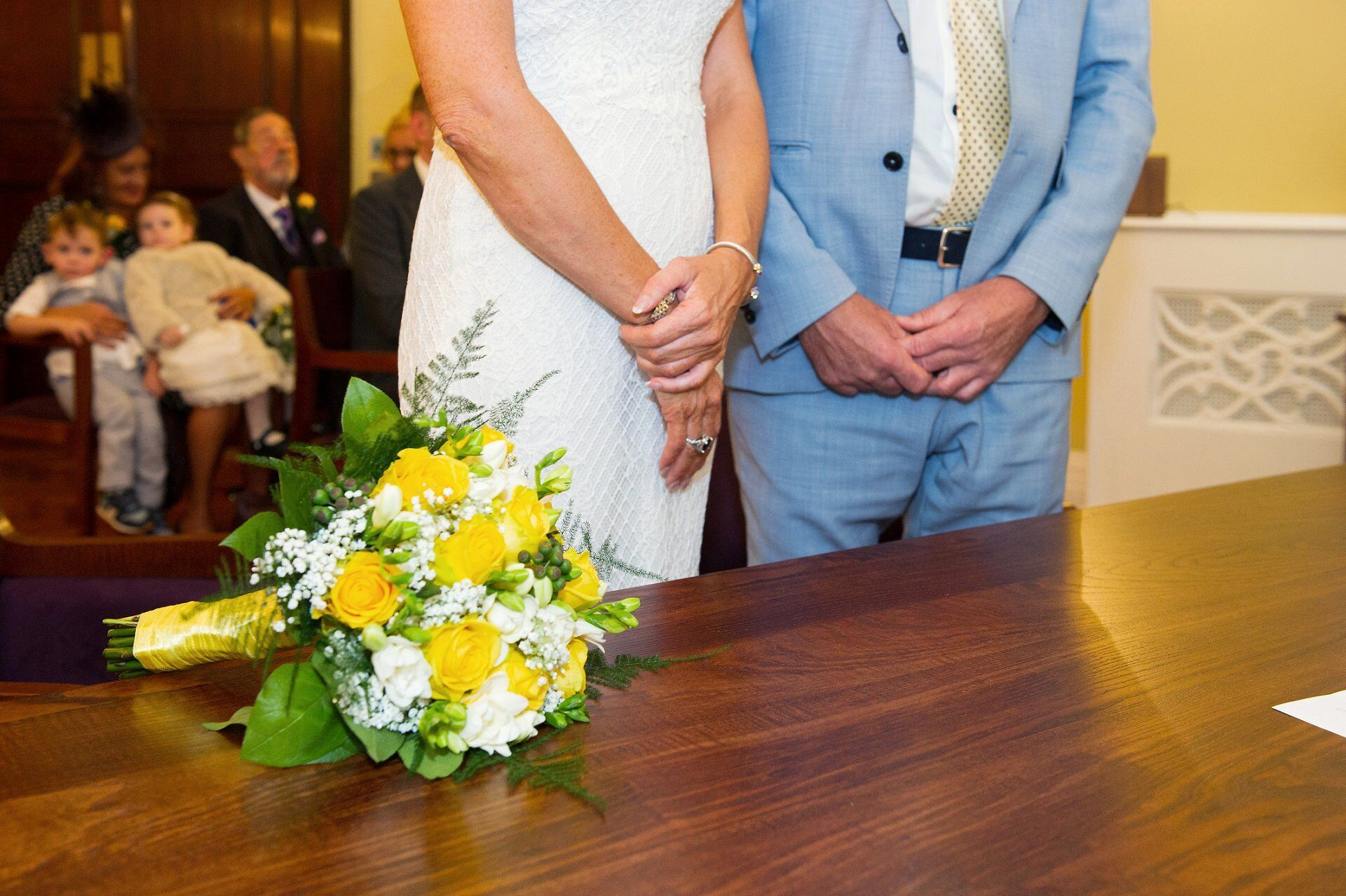 cream and yellow flowers - roses and fresias - on the ceremony table in the brydon room at chelsea old town hall