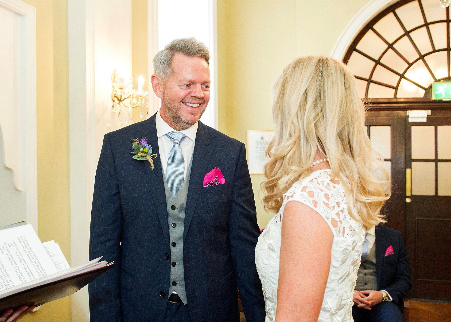 groom smiles at his bride just after they have been annouced as husband and wife in the rossetti room chelsea register office