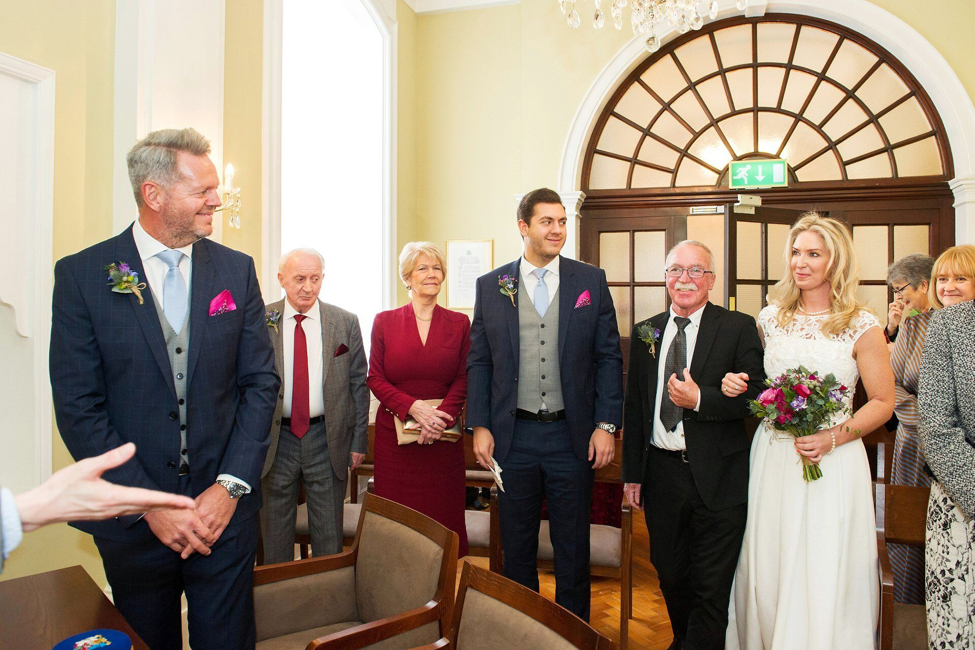 groom turns to see his bride arriving in the rossetti room at chelsea old town hall