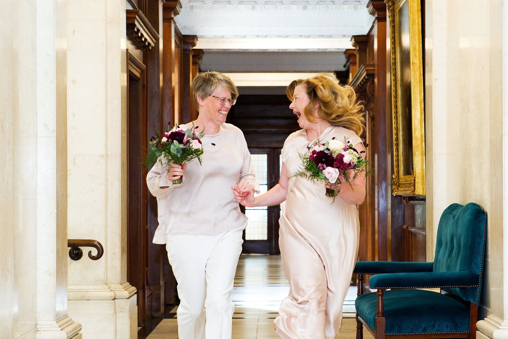 old marylebone town hall wedding photographer captures two brides running along the corrridor after their paddington room ceremony
