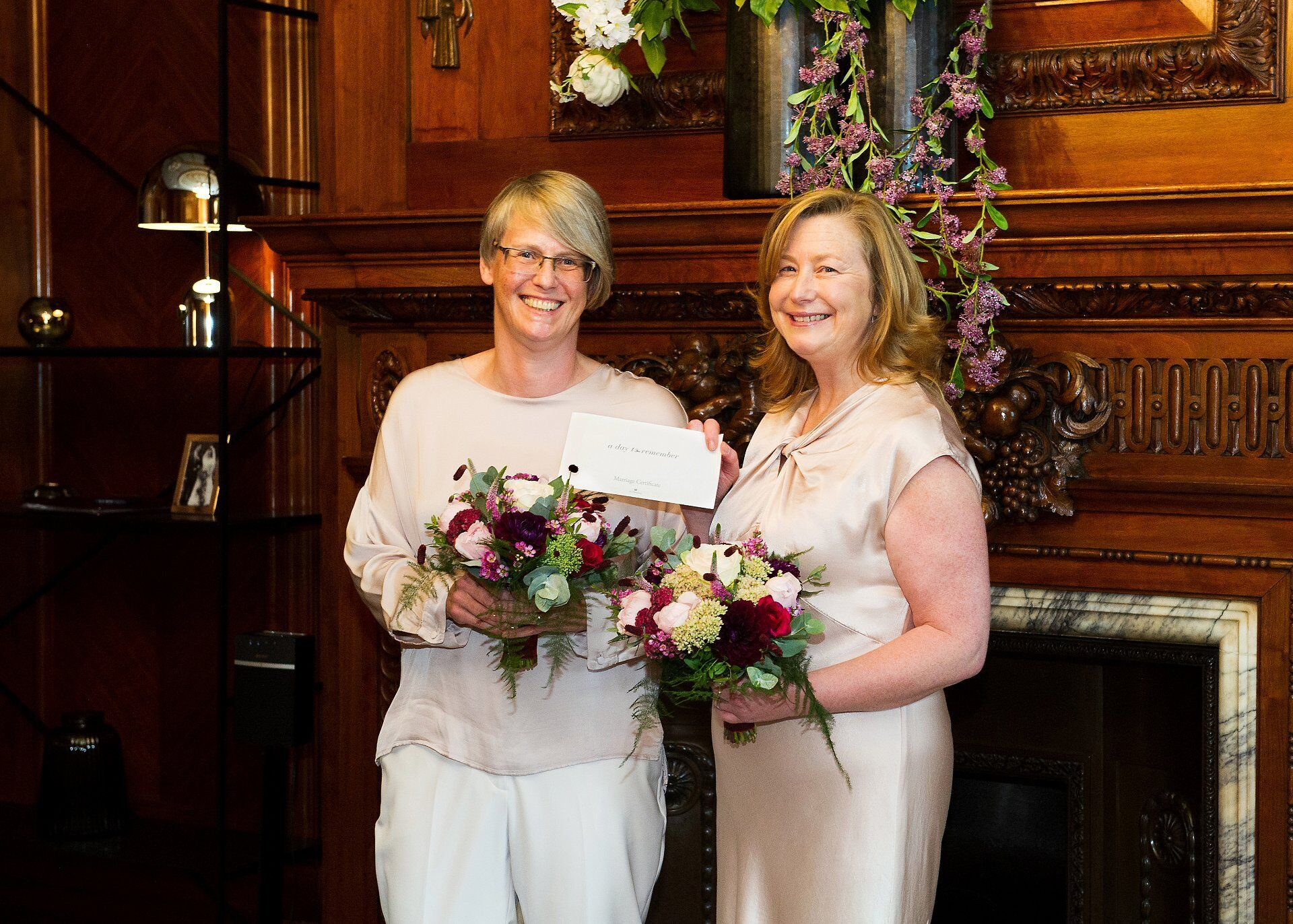 sarah and emma smiling and holding their marriage certificate in the paddington room