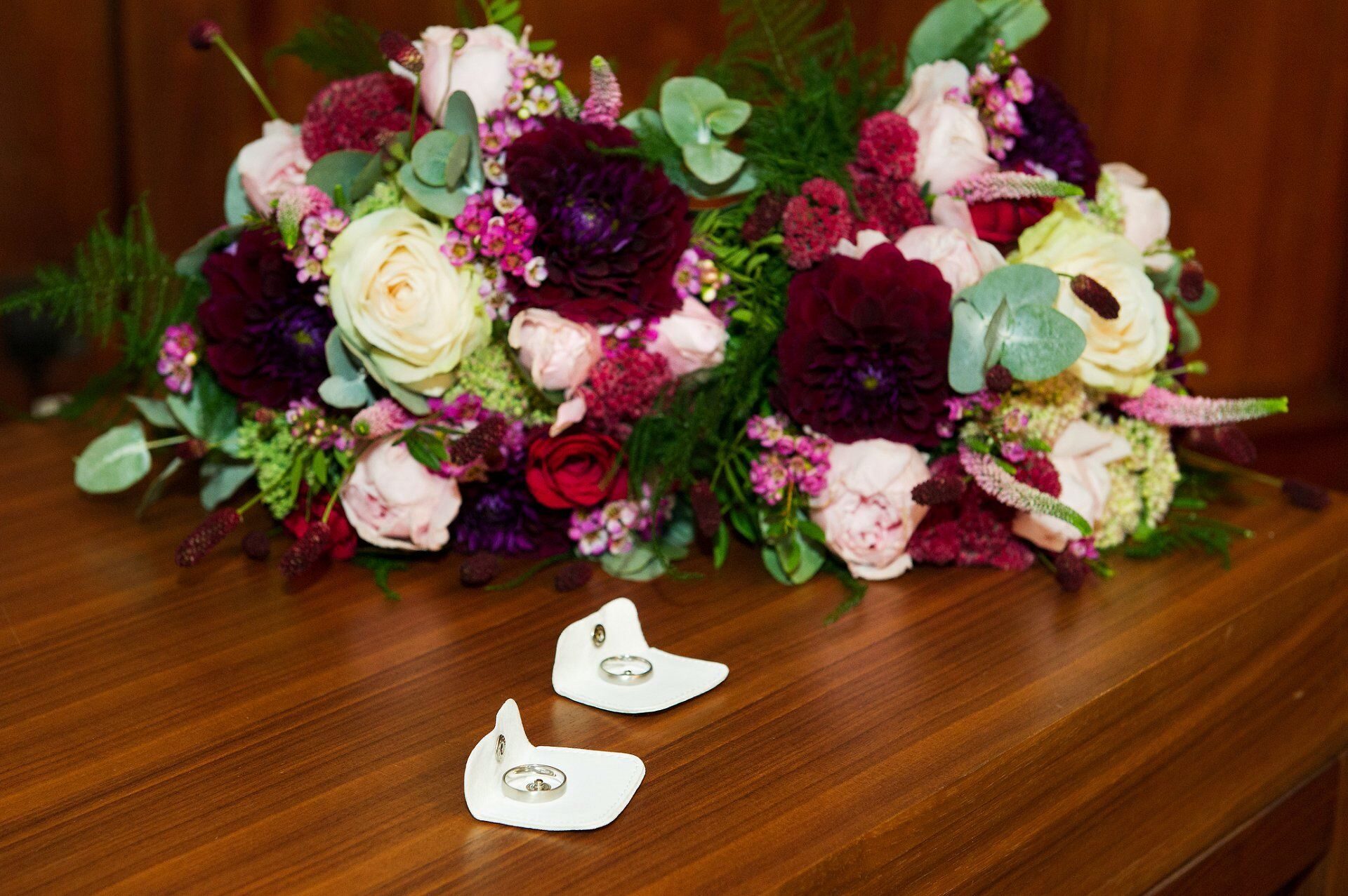 stunning flowers by titanias garden in marylebone and two rings for the two beautiful brides in marylebone registry office's paddington ceremony room