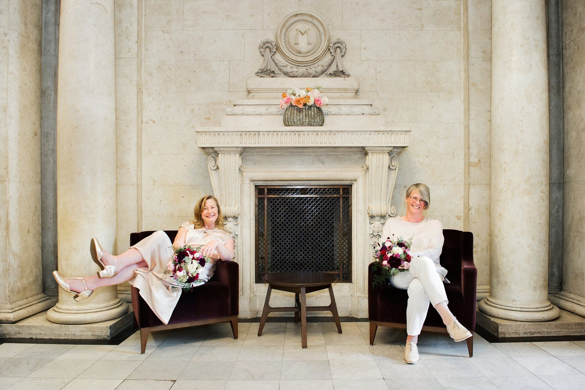 two brides in the lobby at old marylebone town hall sitting on aubergine velvet archairs holding flowers from titainias garden