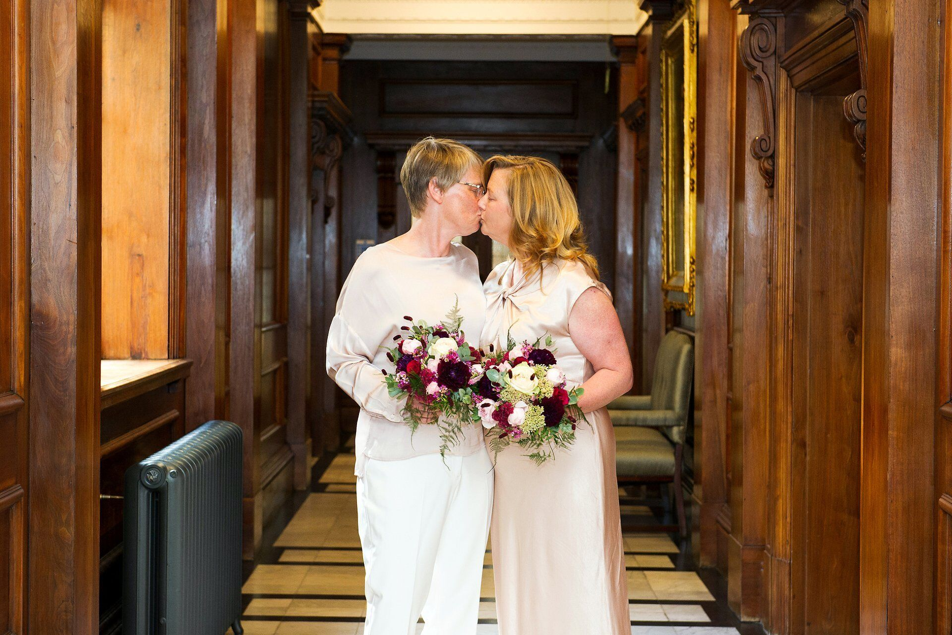 two brides kissing outside the paddington room on the second floor ceremony room level at old marylebone town hall