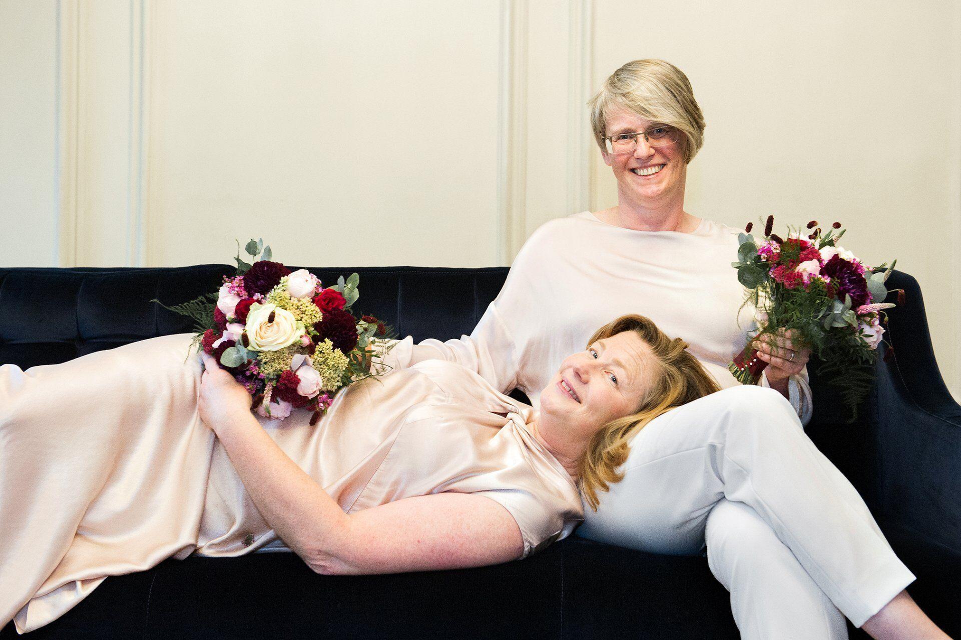two brides relaxing on the navy velvet sofa in the soho room at marylebone register office
