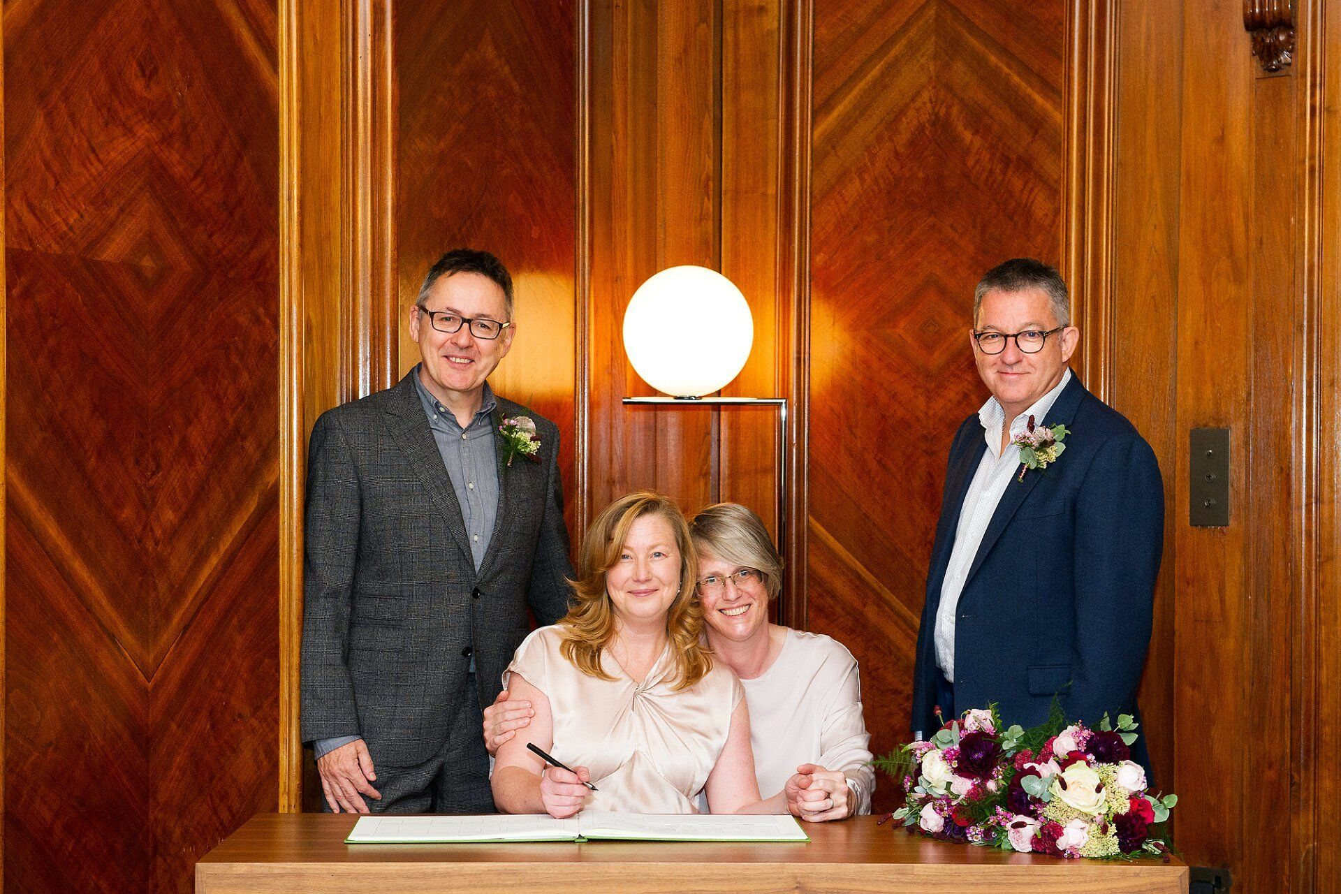 two brides with their two witnesses pose during the signing of the marriage register after their paddington room ceremony