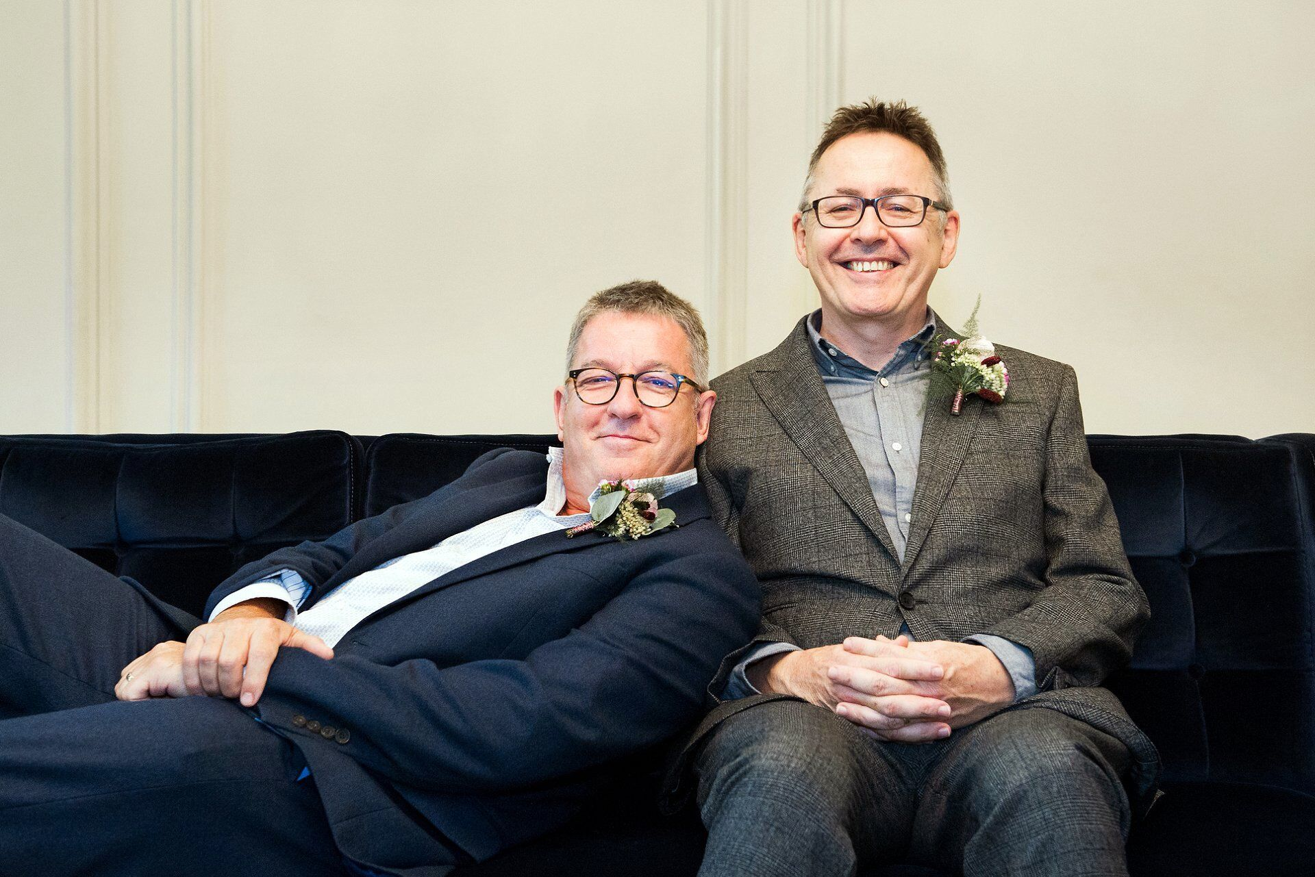 two guests in the soho room at old marylebone town hall on the wonderful navy velvet sofa